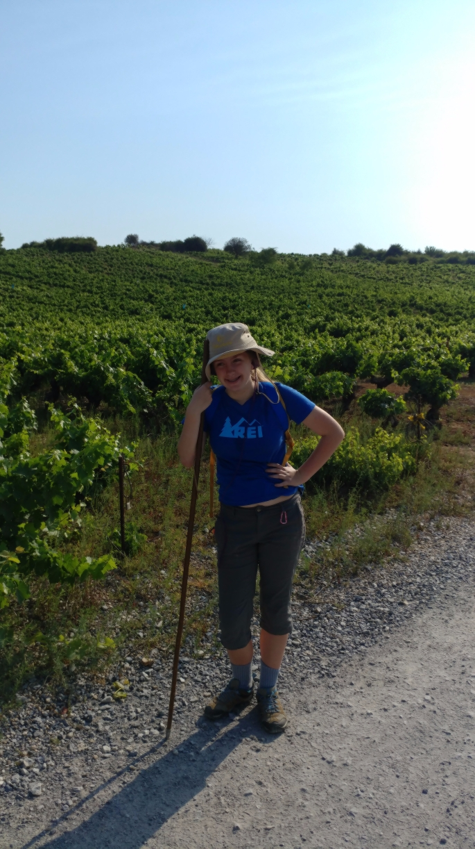 Elizabeth walking through among the grape vines